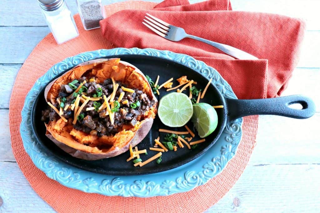 Overhead photo of Tex-Mex Stuffed Sweet Potatoes with Ground Beef & Beans on a blue platter with an orange napkin.