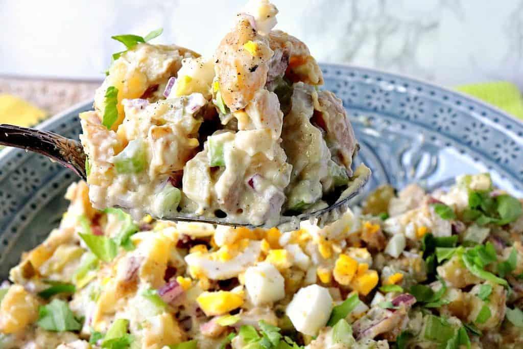 A spoon piled high with creamy Dijon potato salad.
