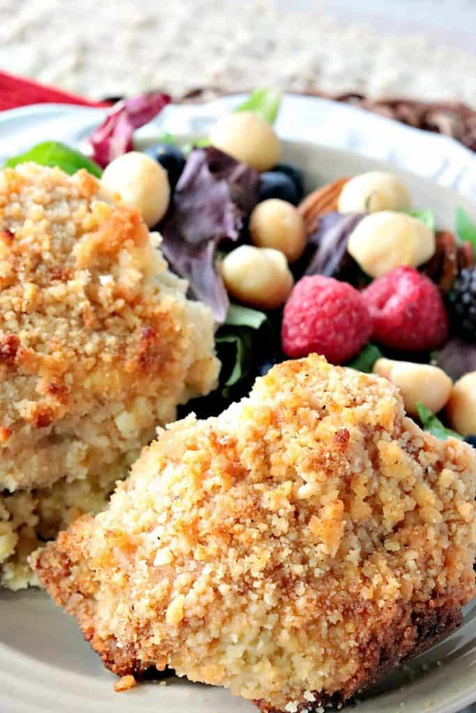 A closeup vertical image of two baked macadamia nut crusted chicken thighs with a salad with berries in the background.