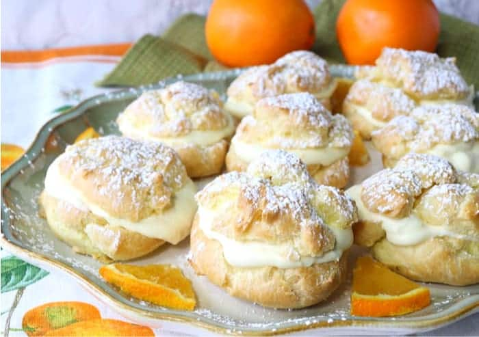 Orange Cream Profiteroles on a platter with oranges in the background and orange slices on the plate.