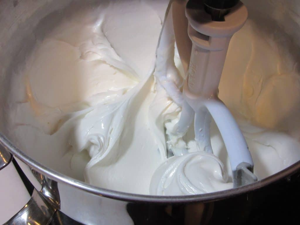 Closeup picture of royal icing in a mixing bowl with a paddle attachment.