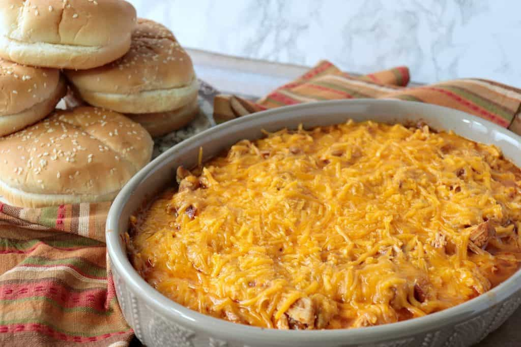 An casserole dish filled with shredded salsa chicken topped with tons of melted cheddar cheese and a pile of buns in the background.