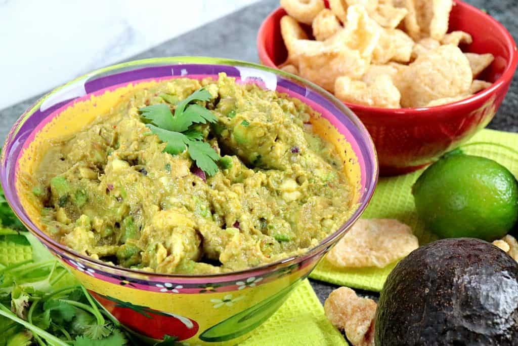 Guacamole in a colorful bowl with cilantro and pork rind dippers in the background.