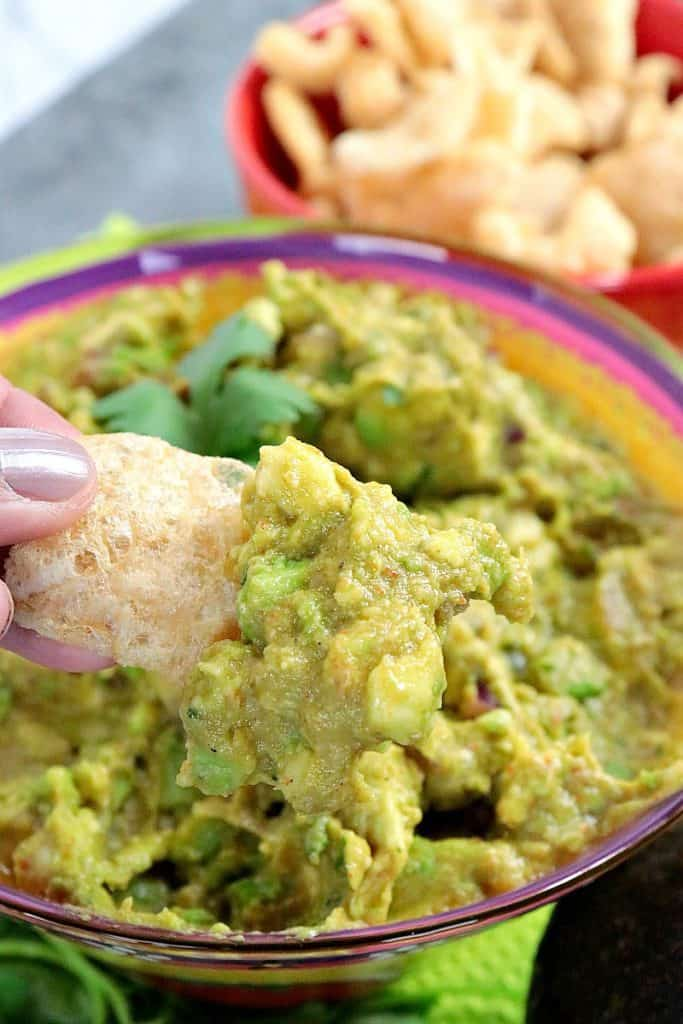 Closeup picture of guacamole on a pork rind chip.