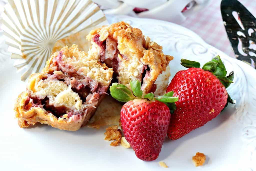 A closeup of the inside of a strawberry crescent muffin on a white plate with strawberries.