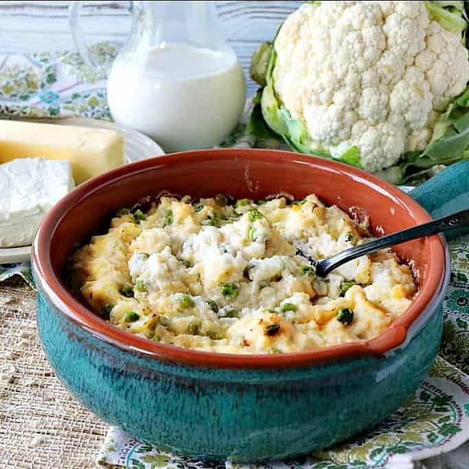 A blue casserole filled with cheesy mashed cauliflower with peas. Butter, cream, and a head of cauliflower are in the background.