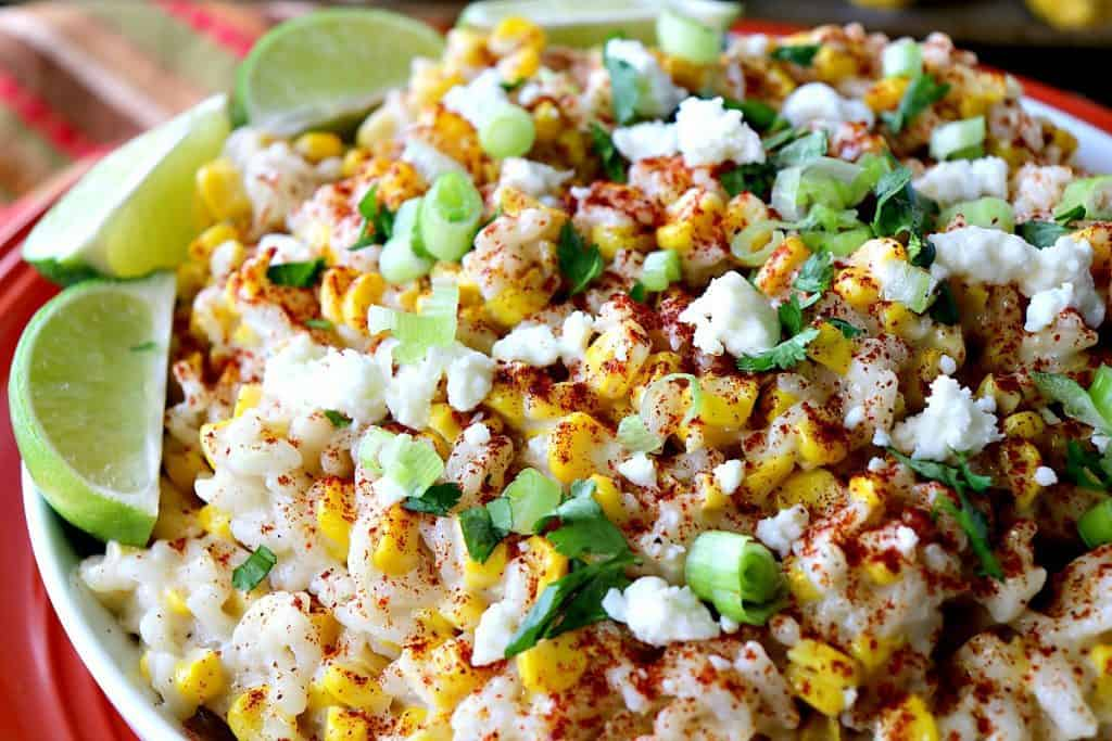 Closeup photo of Mexican street corn risotto with lime wedges, scallions, smoked paprika and cheese.