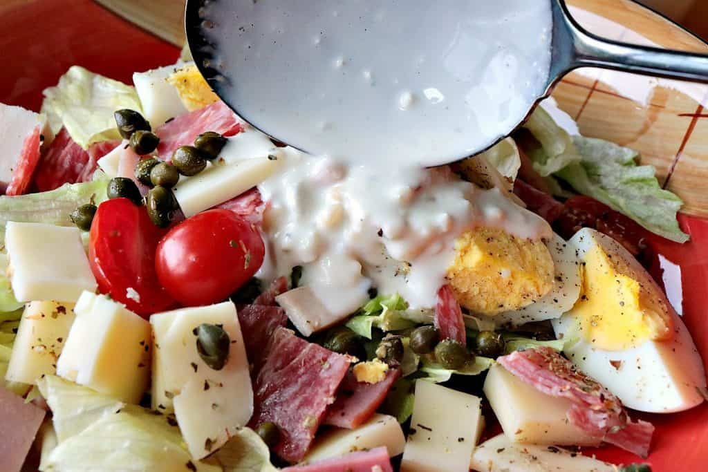 A closeup photo of a salad with meat, cheese, capers, and lettuce with homemade blue cheese dressing.