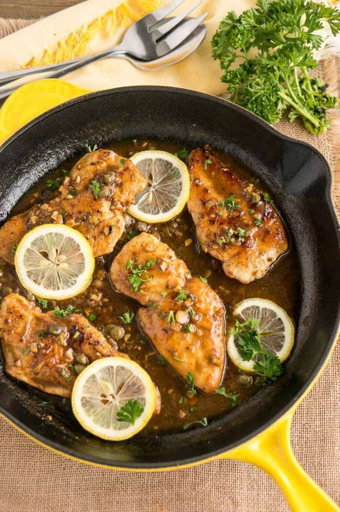 Easy Weeknight Dinner Recipes. Chicken Picatta in a cast iron skillet with lemon and parsley.