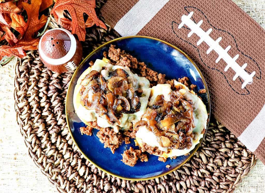 Overhead photo of an open-faced French Onion Sloppy Joes sandwich on a textured place mat and a football napkin.