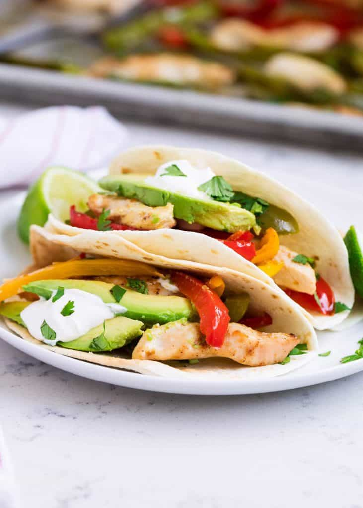 Easy Weeknight Dinner Recipes. Chicken Tacos on a plate with avocado, peppers, and limes.