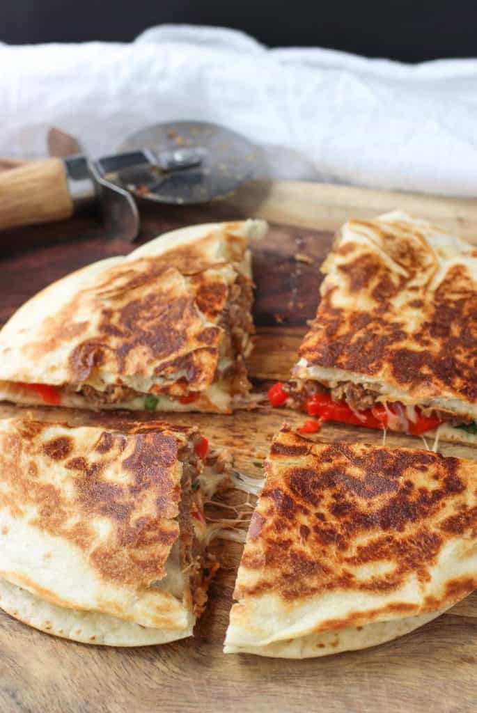 Easy Weeknight Dinner Recipes. Four sliced quesadillas with a pizza cutter in the background.