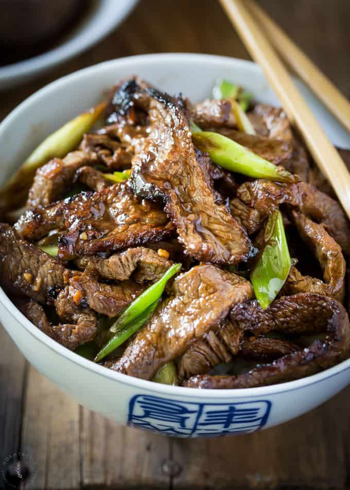 Easy Weeknight Dinner Recipes. Beef strips in a blue and white bowl with scallions.