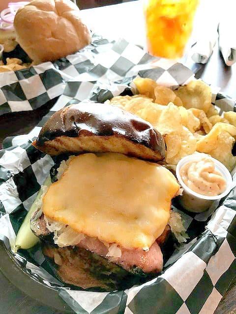 Overhead photo of a Knockwurst sandwich on a pretzel roll.