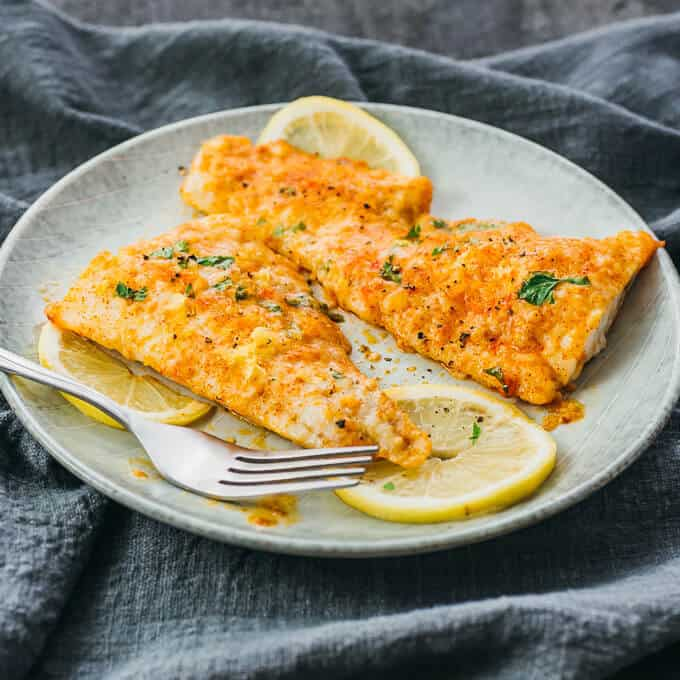 Easy Weeknight Dinner Recipes. Two fish fillets on a plate with lemon slices and seasoning.