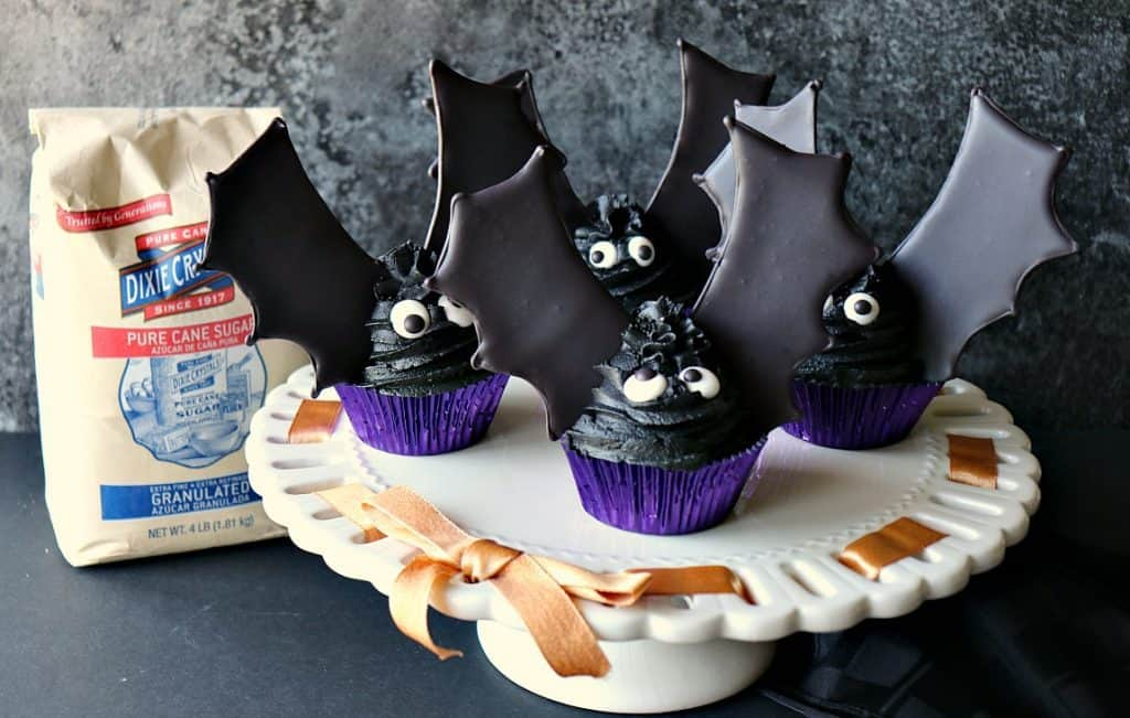 A flock of bat wing cupcakes on a white cake stand with orange ribbon