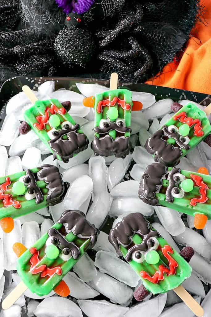 A bunch of frozen Frankenstein pudding pops on a tray with ice and orange and black napkins in the background.