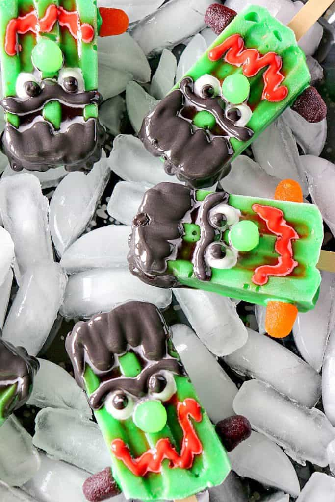 An overhead vertical image of frozen Halloween pops with scary faces.
