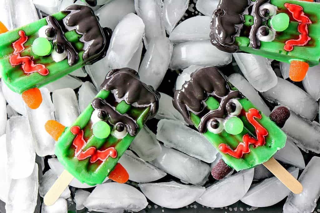 Overhead photo of a tray of ice with frozen Halloween pudding pops with scary faces.