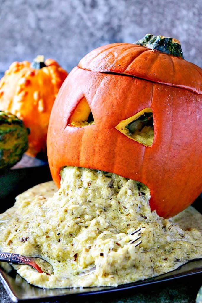 Vertical closeup photo of a carved pumpkin with spaghetti squash vomit for Halloween.