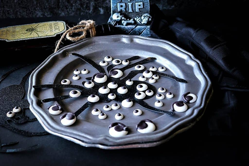 Spooky horizontal photo of a gray plate of candy eyeballs with a spider silhouette and black napkin.