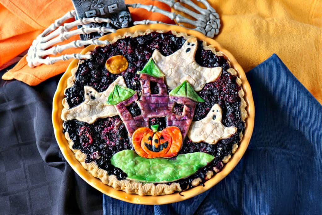 Overhead photo of a Halloween Pie with colorful napkins, ghosts, pumpkins, and skeleton hands.