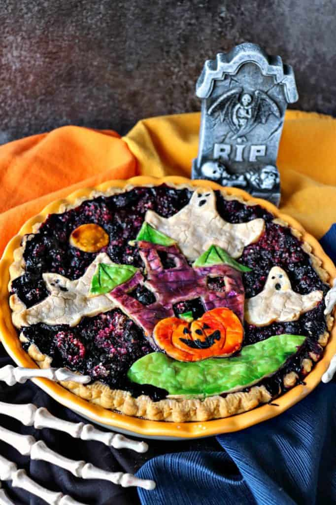 Vertical close up image of a Halloween pie with ghosts, haunted house, and pumpkins. Boo berry pie.