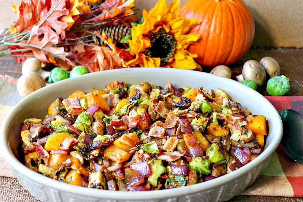 An oval casserole dish filled with colorful sauteed autumn vegetables of Brussels sprouts, mushrooms, butternut squash, and bacon. Pumpkin, mushrooms and a sunflower are in the background.