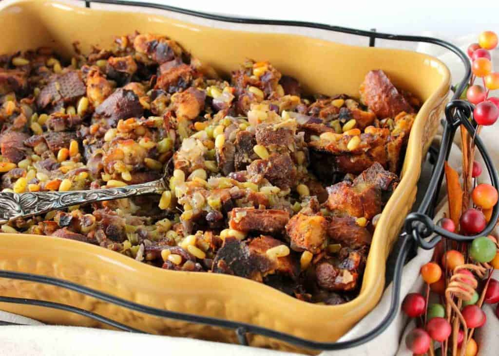 A casserole dish filled with pretzel roll stuffing and a serving spoon. Popular Thanksgiving side dish recipe roundup.