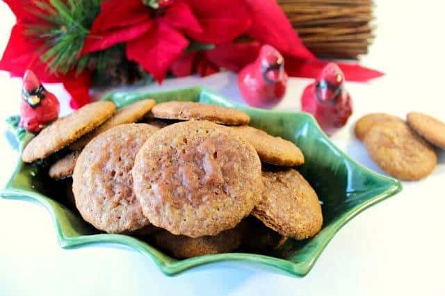 A closeup photo of soft gingerbread cookies in a holly berry dish with a cardinal for a Christmas cookie recipe roundup.