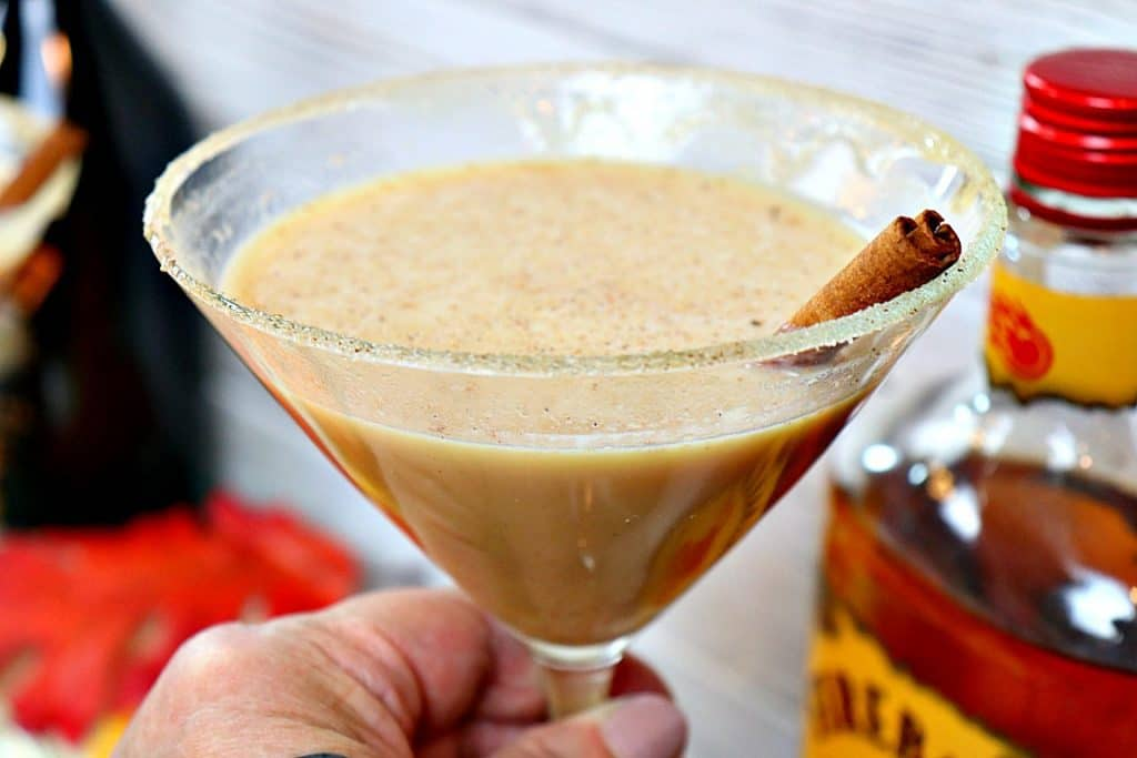 Closeup photo of a pumpkin spice martini with a cinnamon stick and a sugar cinnamon rim.
