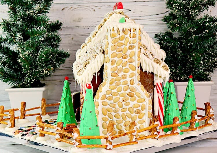 Side view of decorated gingerbread house with peanut and royal icing chimney, pretzel fence and sugar cone iced pine trees. - kudoskitchenbyrenee.com