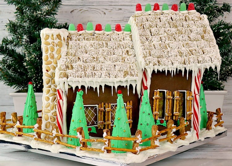 Back of a decorated gingerbread house with snow, candy, icicles, and in a snowy yard with a fence. - kudoskitchenbyrenee.com