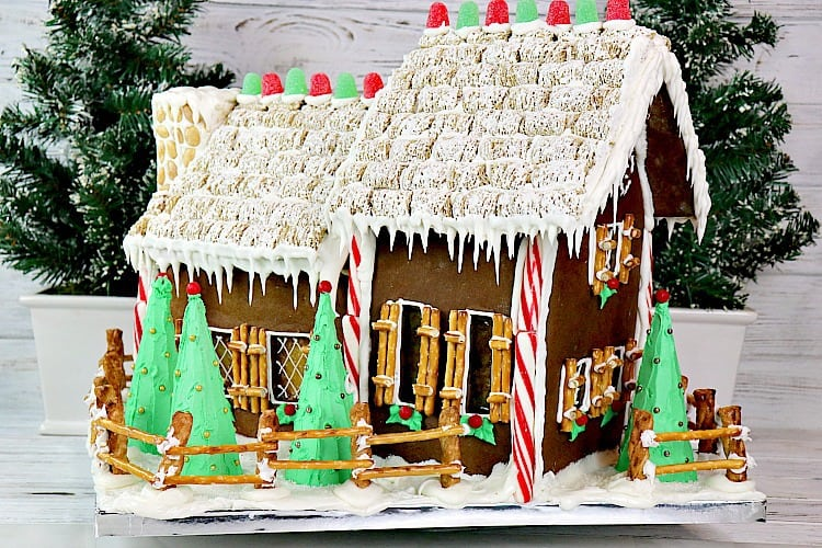 Decorated gingerbread house with candy windows, pretzel shutters, snow covered yard, mini wheat roof, and gumdrop accents. - kudoskitchenbyrenee.com