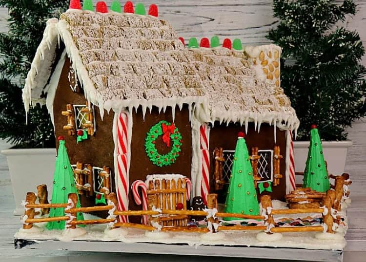 Horizontal photo of a gingerbread house with frosted wheat roof, candy cane sides, and a pretzel fence.
