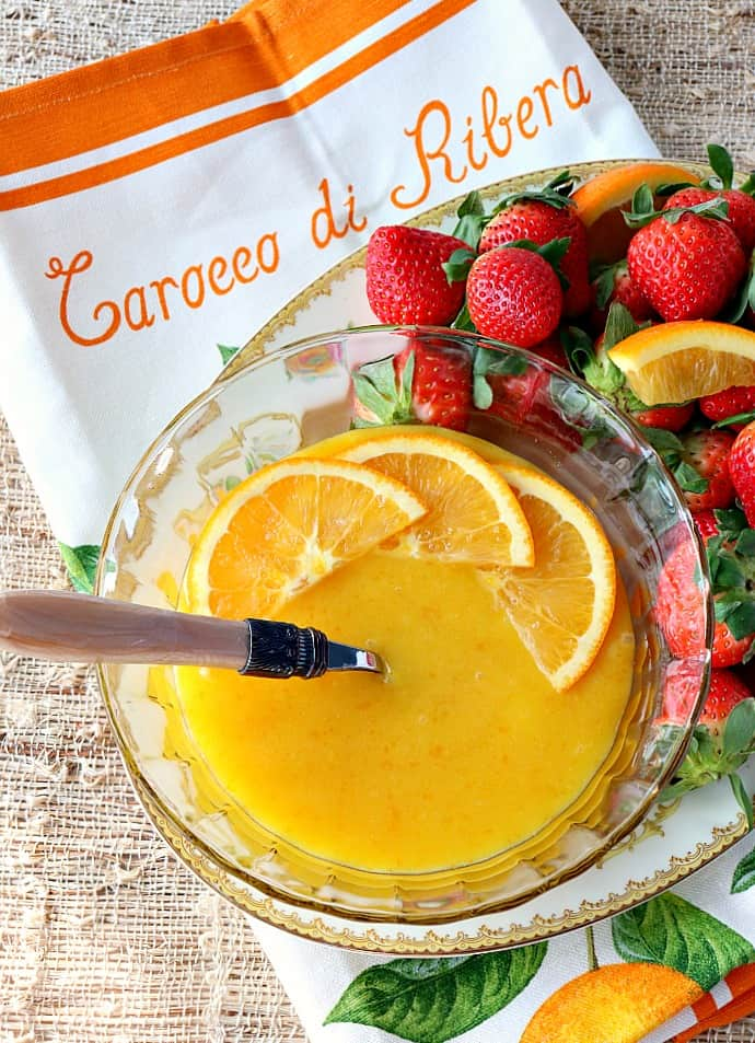 Overhead vertical image of a bowl of homemade orange curd with strawberries and orange slices.