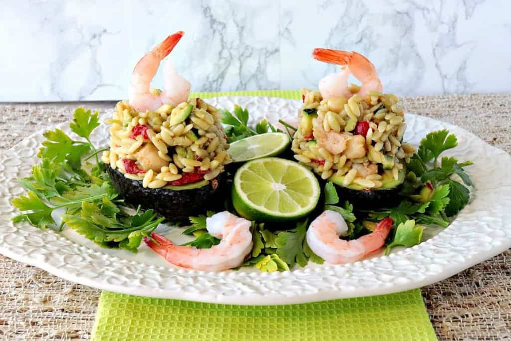 Two orzo stuffed avocados on a plate with lettuce, limes and shrimp. - Kudos Kitchen by Renee