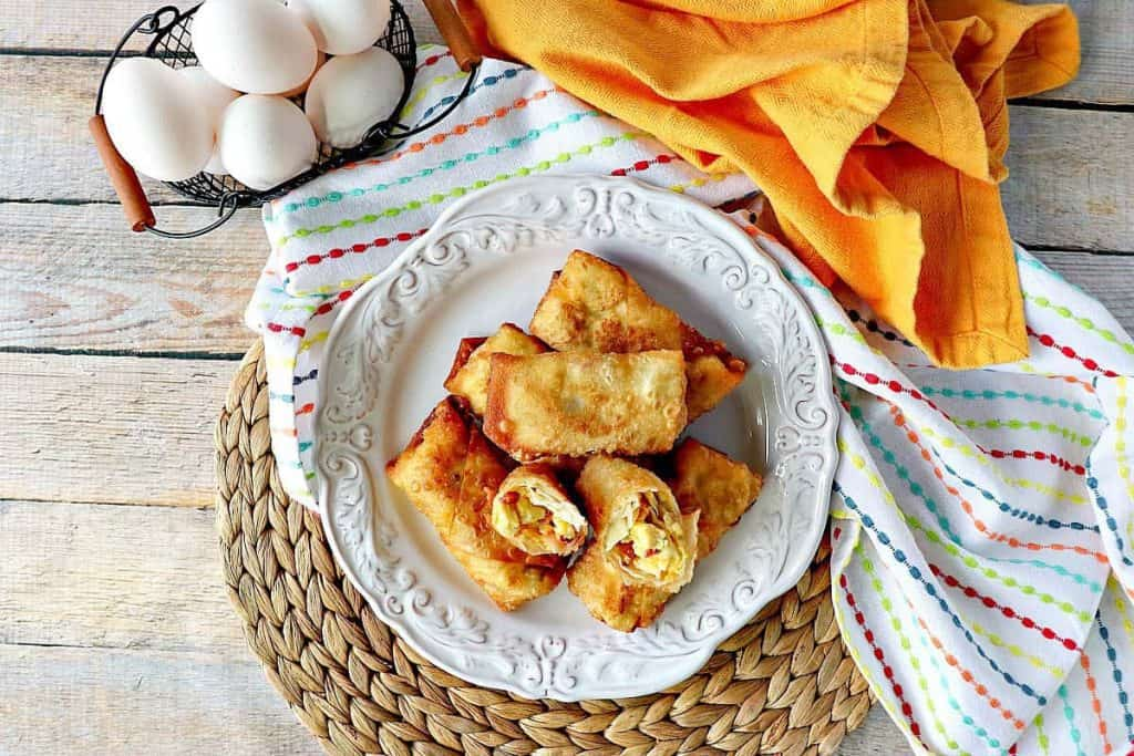 Scrambled Egg Rolls on a plate with a yellow napkin and eggs - kudoskitchenbyrenee.com