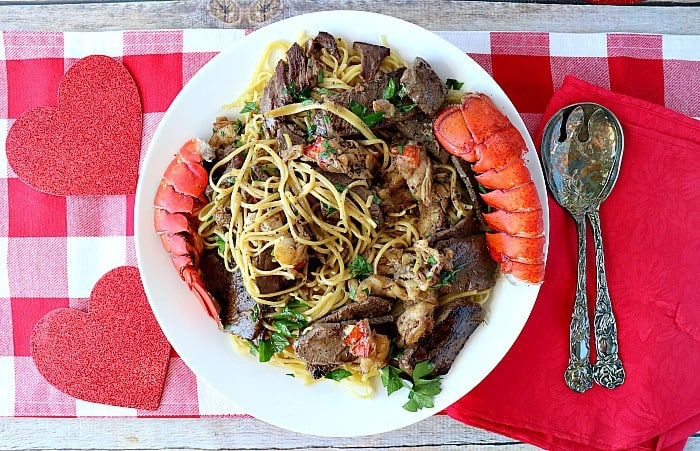 An overhead photo of a large pasta bowl filled with steak and lobster linguine with lobster tails on the side, a red and white checked table cloth, and serving utensils.