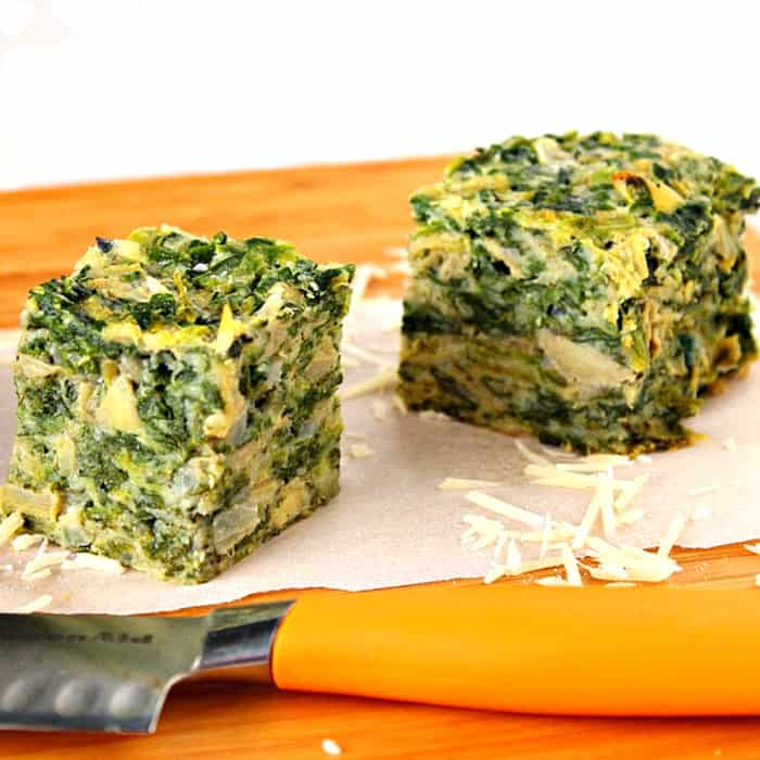 Closeup picture of two spinach appetizer squares on a cutting board.