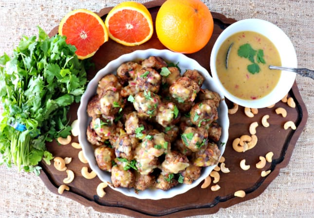Overhead picture of a dish of turkey meatballs with sauce, cashews, oranges, and cilantro.