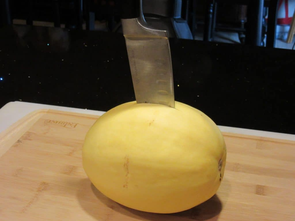 Spaghetti squash with a chef's knife inserted in the center.