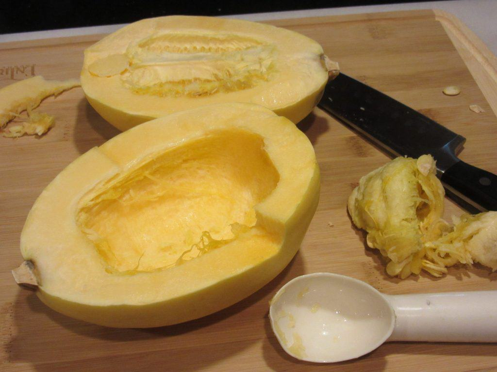 Split open spaghetti squash with the seeds taken out and an ice cream scoop