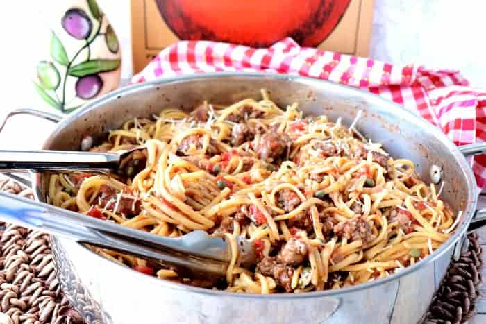 Pan of linguine pasta with tomatoes, sausage, capers and tongs.
