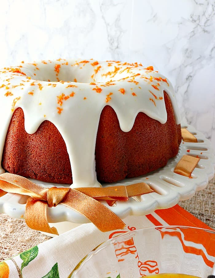 Bundt cake with a thick white icing and orange zest on a white plate with a orange ribbon.