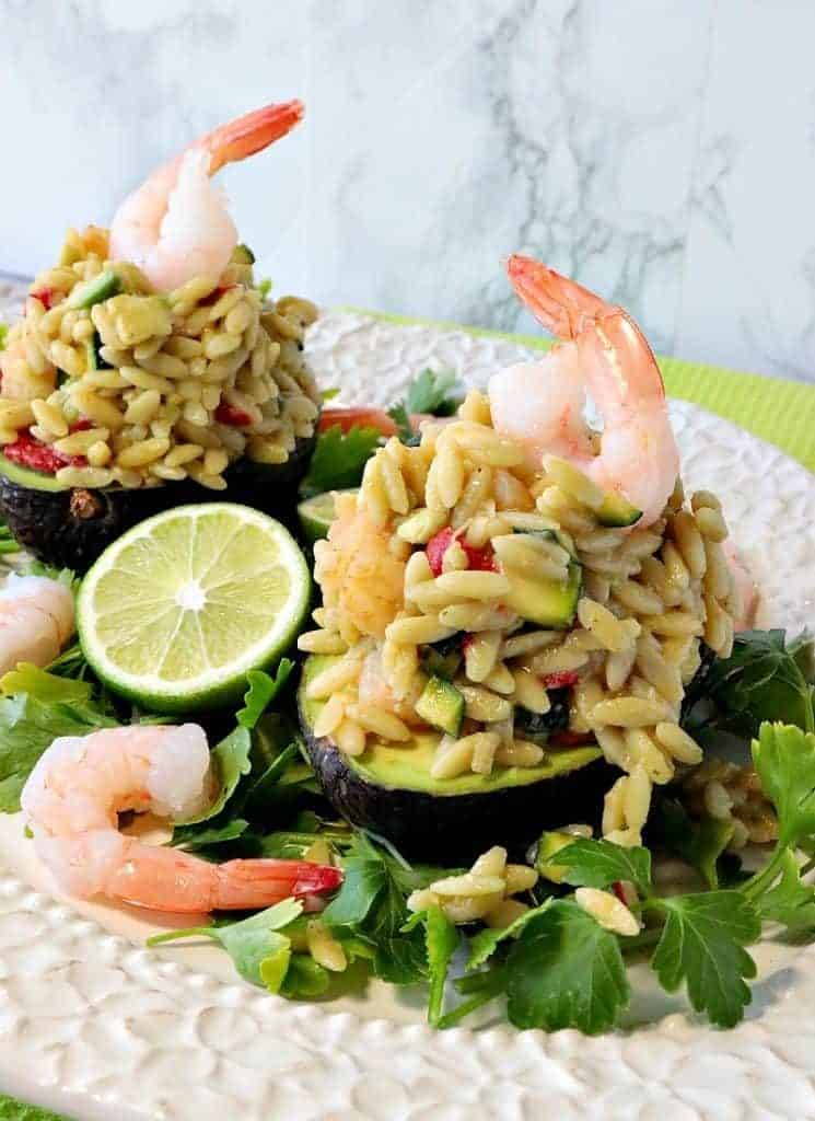 Two Orzo pasta and shrimp salad stuffed avocados with cooked shrimp on the top and a wedge of lime.