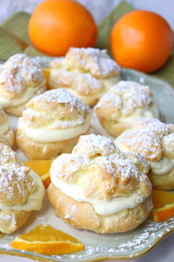 Vertical picture of a plate of orange eclairs with orange whipped cream