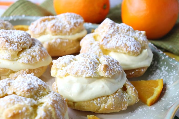 Closeup picture of profiterole with orange cream filling and a confectioners sugar dusting