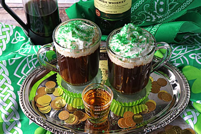 Two mugs of Irish Coffee on a silver platter with whipped cream and green sugar
