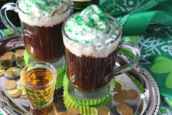 Shot of whiskey and a mug of Irish coffee on a sliver tray with whipped cream and green sugar